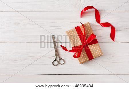 DIY hobby background. Making box for christmas or other holiday handmade present in craft paper with red ribbon. Scissors on white wooden table, top view with copy space
