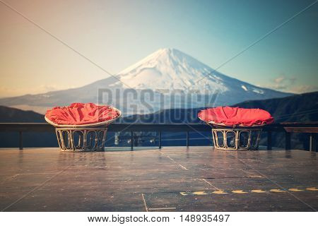 Chairs made of rattan and upholstery fabrics in red on wooden terrace with Mount Fuji background.