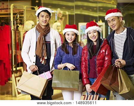 group of young asian people shopping together for christmas