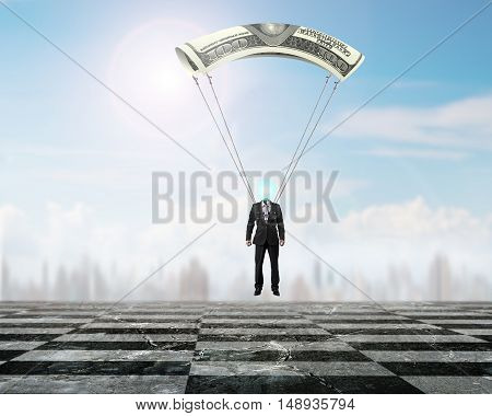 Businessman With Money Parachute Landing On Chessboard Ground