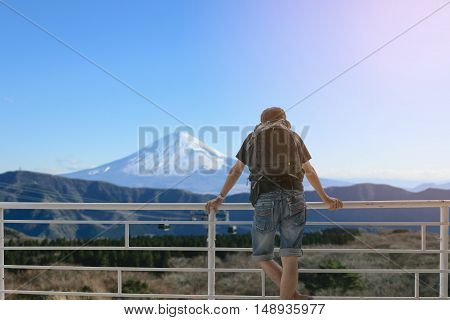 Backpacker standing on the balcony and look at Mount Fuji in Japan.
