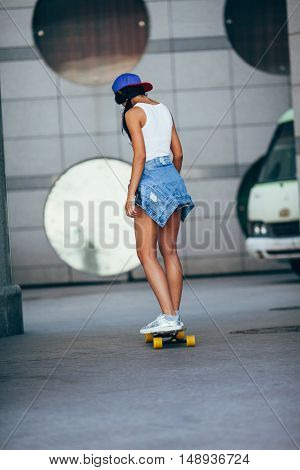 yong fashion brunette riding on wooden longboard before round windows