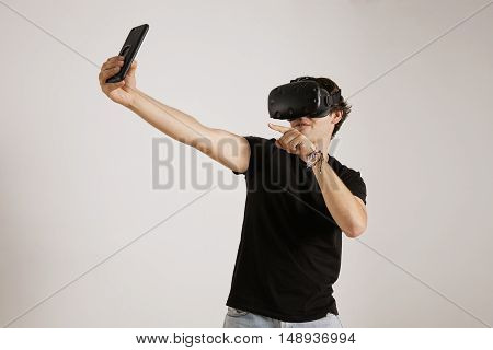 A young gamer in black t-shirt and VR headset posing for a selfie on his smartphone against white wall