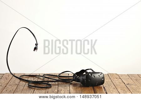 VR headset and some cords on a rough rustic wooden table against white wall background