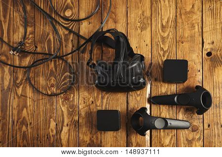 VR headset and gaming accessories with cords on a brown wooden table
