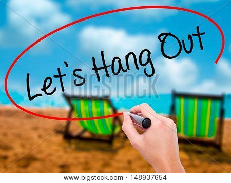 Man Hand Writing Let's Hang Out With Black Marker On Visual Screen