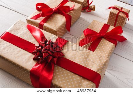 Lots of Gift boxes on white wood background. Presents in craft paper decorated with red ribbon bows. Christmas and other holidays concept.