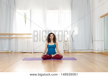 Curly brunette girl sitting in lotus position on mat indoors with eyes closed