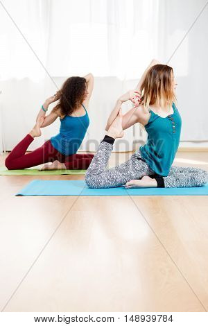 Two attractive women doing asana one legged king pigeon and meditate with eyes closed indoor
