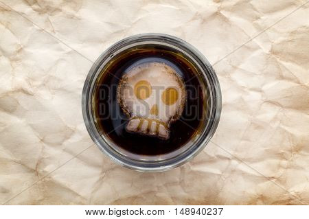 Glass of drink with skull shape ice top view