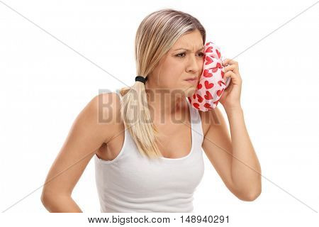 Young woman having a toothache and holding an ice pack isolated on white background
