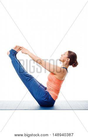 Beautiful sporty fit woman practices Ashtanga Vinyasa Yoga asana Ubhaya padangusthasana - both big double toe pose balance posture isolated on white