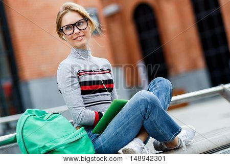 Girl in glasses and headphones sitting on street in front of building