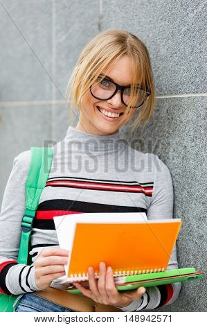 Smiling student with open book and backpack on shoulder at grey walls
