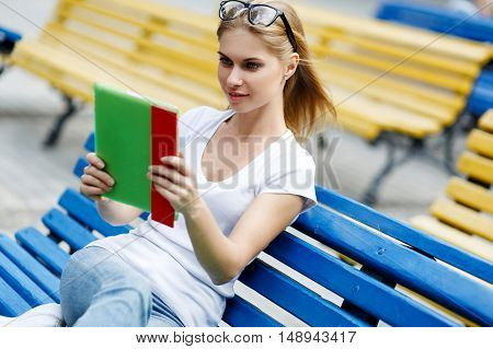 Young woman looks into tablet computer sitting on bench in Park