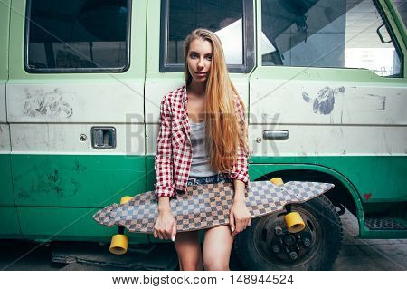 seriously young beautiful blonde woman with longboard standing near green bus and looking to the camera