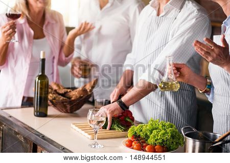 Smells so fine Nicely dressed people preparing meal together while having some red wine
