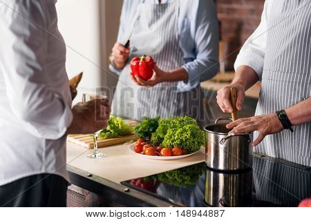 Three in the kitchen. Female hands cutting bell pepper, one male stirring something in the pot, while another male holding glass of white wine