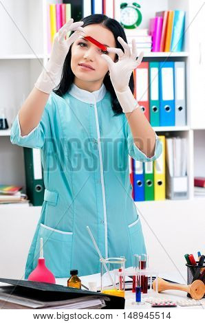 Female medical or scientific researcher or woman doctor working with samples in hospital. Beautiful young woman lab assistant studying blood sample for analysis. Health nurse working in laboratory.