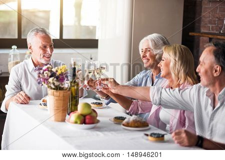 Cheering. Happy mature white family raising glassed at dinner table