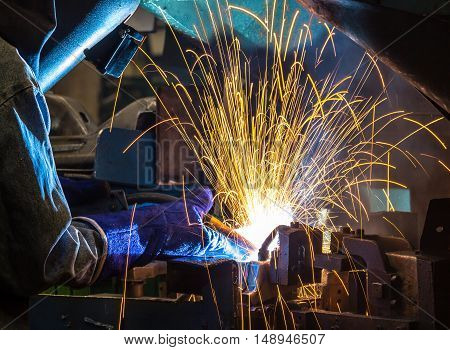 The worker with protective mask welding metal