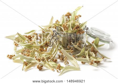 Dried linden flower in a jar isolated on white background. The flowers resemble miniature umbrellas with yellowish color have a strong flavor and are used for making tea. Linden blossom has a disinfectant anti-inflammatory and diuretic.