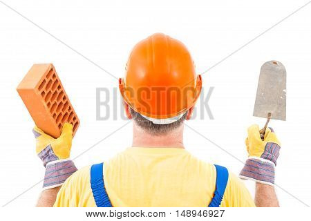 Construction worker with hard hat and gloves holding trowel and brick in his hands isolated on white background.