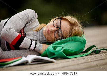 student in glasses fell asleep on wooden stage before books