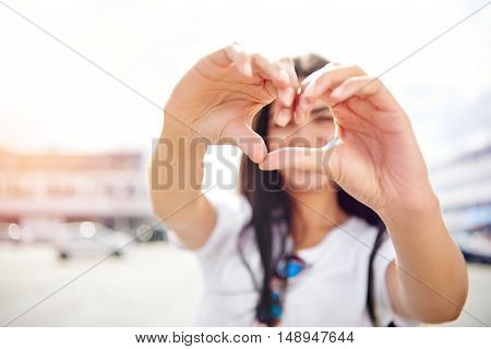 Romantic young woman making a heart gesture as a symbol of her love for her sweetheart or as a flirting teasing sign