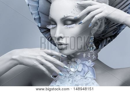 Closeup portrait of beautiful young woman dressed as winter queen. Creative makeup. Over grey background. Copy space.