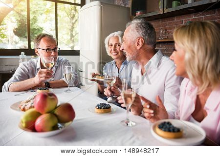 Vivid. Old man in glasses telling stories to his friends while having drinks and desserts