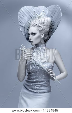 Portrait of beautiful young woman dressed as winter queen. Creative makeup. Over grey background. Copy space.