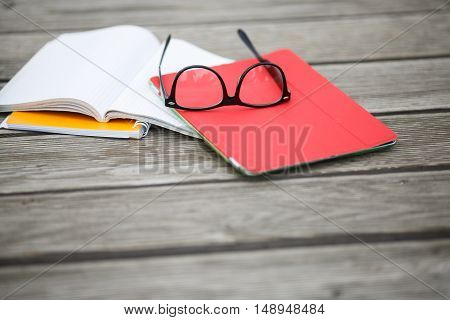 Glasses and notebooks lie on wooden floor.Accessories for student.Accessories for student