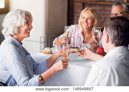 Sincere. Grey-haired lady smiling at toasts and wishes while taking little berry cake
