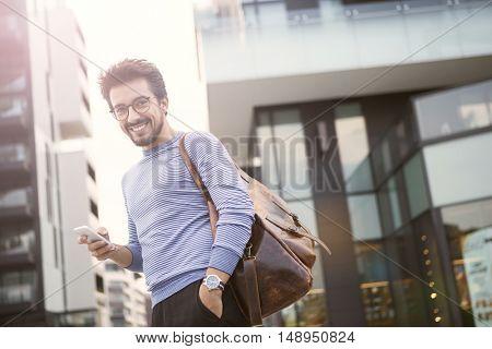 Smiling man carrying a vintage bag