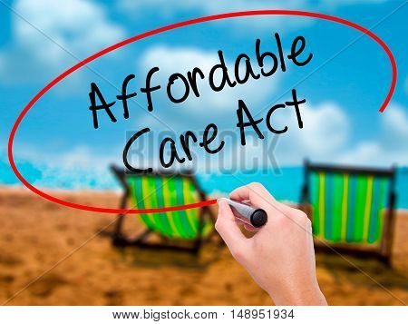 Man Hand Writing Affordable Care Act With Black Marker On Visual Screen