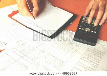 Hand making notes in a notebook with a pen over documents and using counting calculator at home or office savings finances economy and concept.