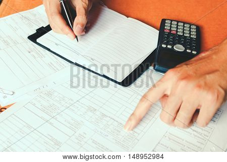 Hand making notes in a notebook with a pen and using counting calculator at home or office savings finances economy and concept.