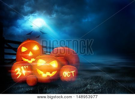 A group of halloween Jack O Lantern pumpkins with smiling faces glowing in the evening moonlight.
