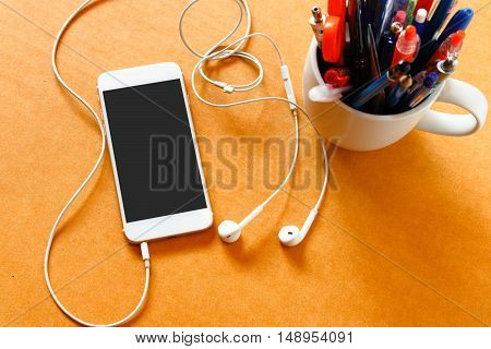 Smartphone with blank screen gadjet in cup and earphones on wooden background