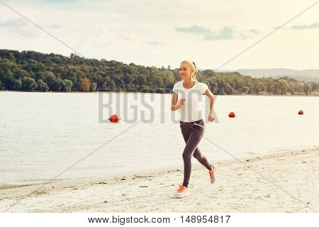 Woman jogging at beach by the river