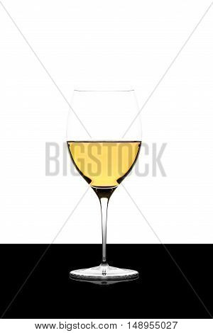 white wine glass on a black board isolated and backlit