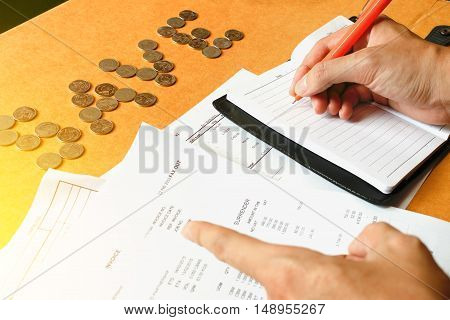 Human hand holding pen writing note coins text 'save' on desk savings finances economy and home concept