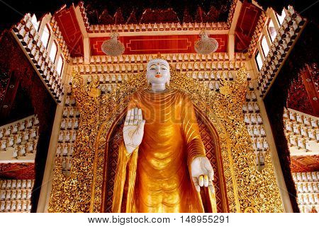 Georgetown Malaysia - January 8 2008: A benevolent gold-robed giant alabaster Buddha in the great hall of the Dhammikarama Burmese Buddhist Temple