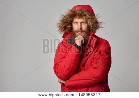 Portrait of pensive bearded man in red winter jacket with hood on, over grey background