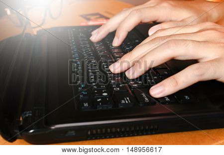 Close up woman working at home officefingers using touch texting on a computer laptop keyboard