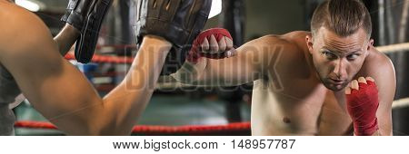 Focused and confident boxer punch during training in the ring