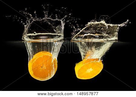 Group of fresh fruits falling in water with splash on black background.