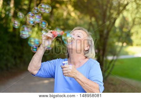 Happy Senior Woman Having Fun Blowing Bubbles