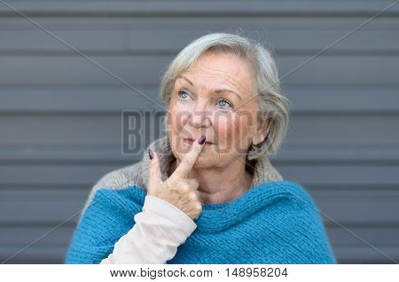 Thoughtful stylish senior woman looking up into the air with her finger to her lips and a contemplative expression against a grey wall
